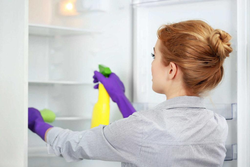 Женщина моет холодильник