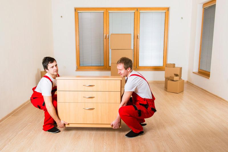 Грузчики несут мебель