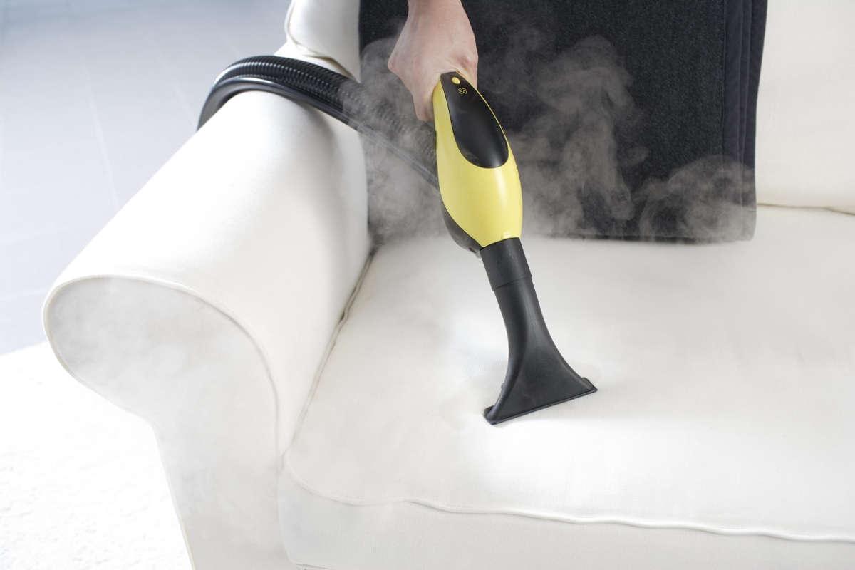Хозяйка пылесосит диван