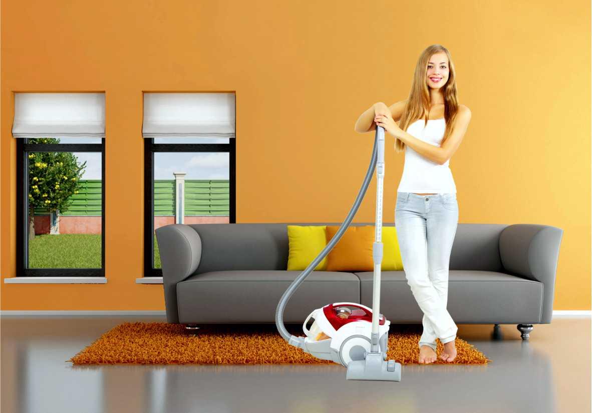 Девушка с пылесосом стоит у дивана