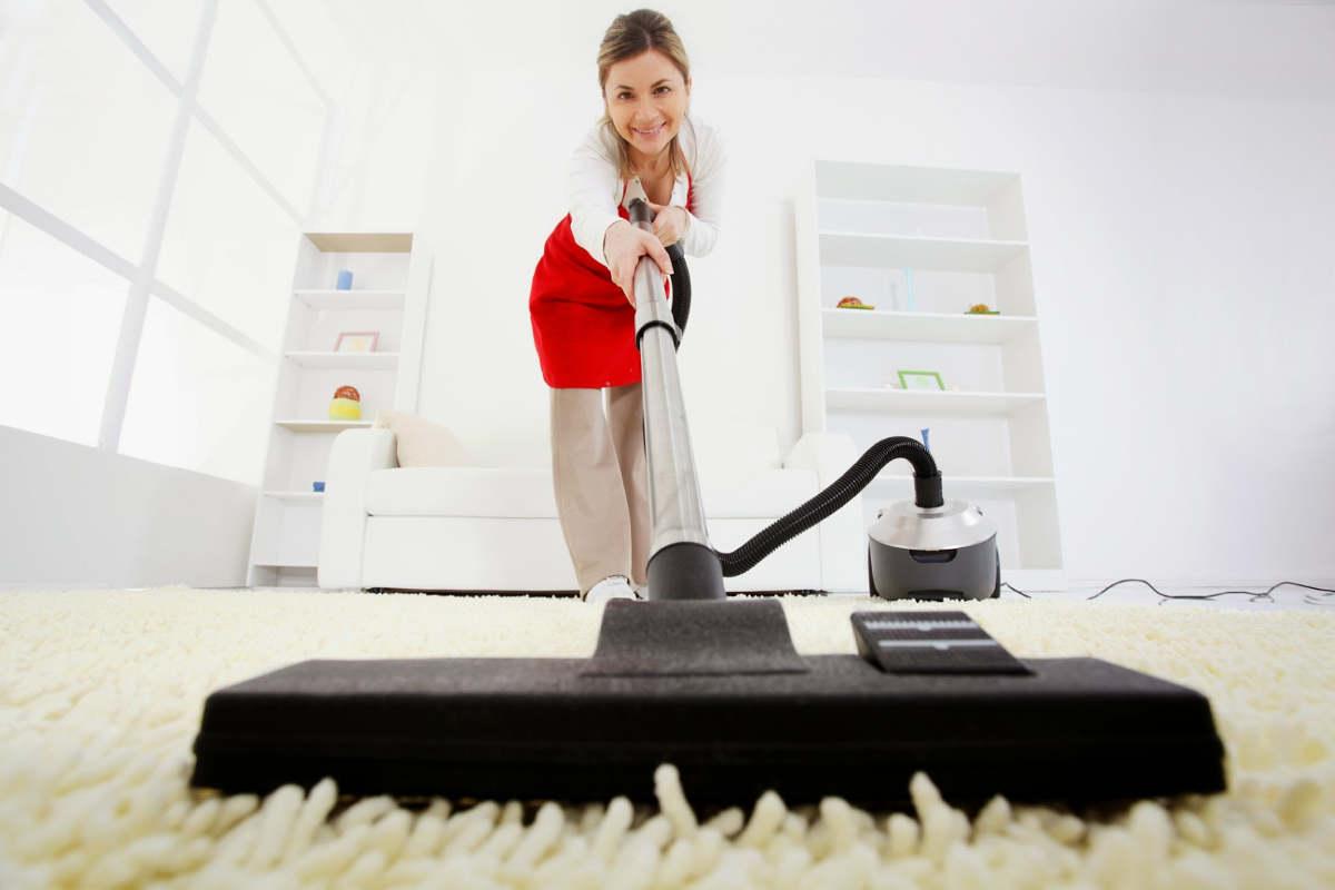 Девушка пылесосит ковёр