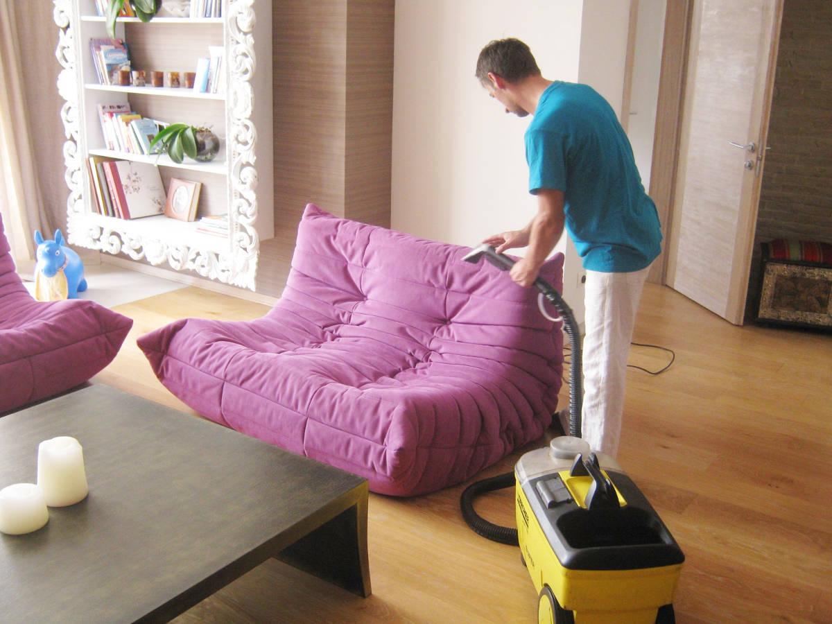 Мужчина пылесосит диван