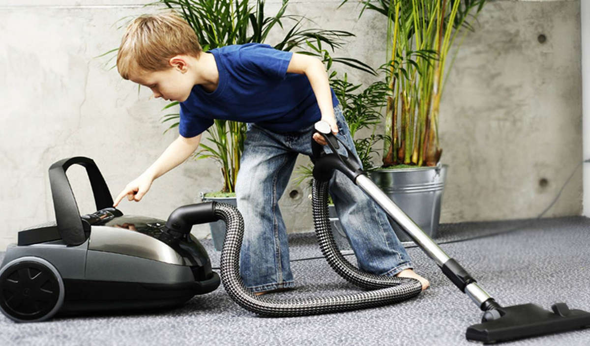 Мальчик включает пылесос