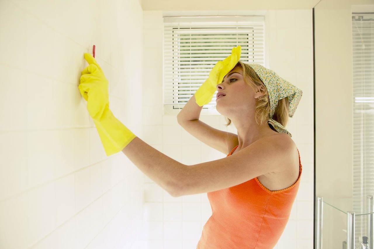 Женщина моет стену