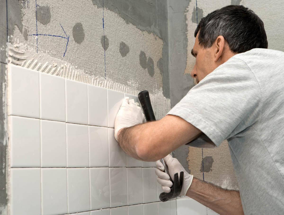 Рабочий укладывает плитку на стену