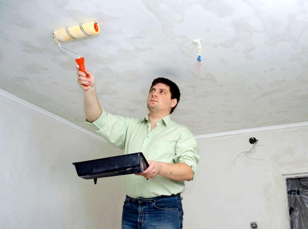 Мужчина моет потолок