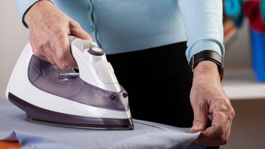 Мужчина гладит утюгом одежду