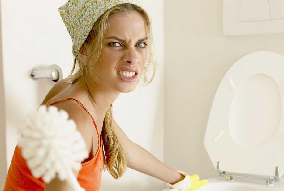 Женщина чистит унитаз
