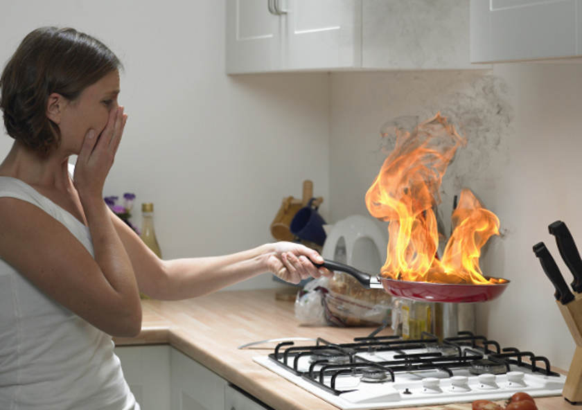 Хозяйка на кухне со сковородой в руках