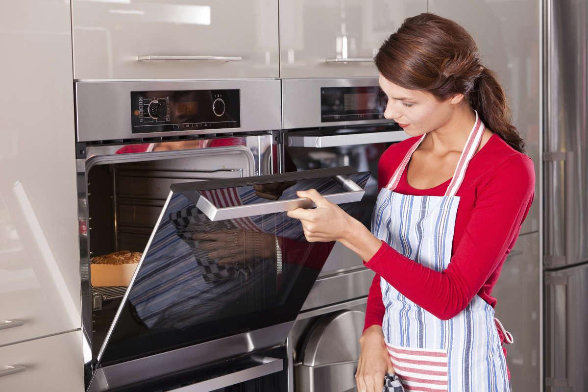 Хозяйка у духовки на кухне