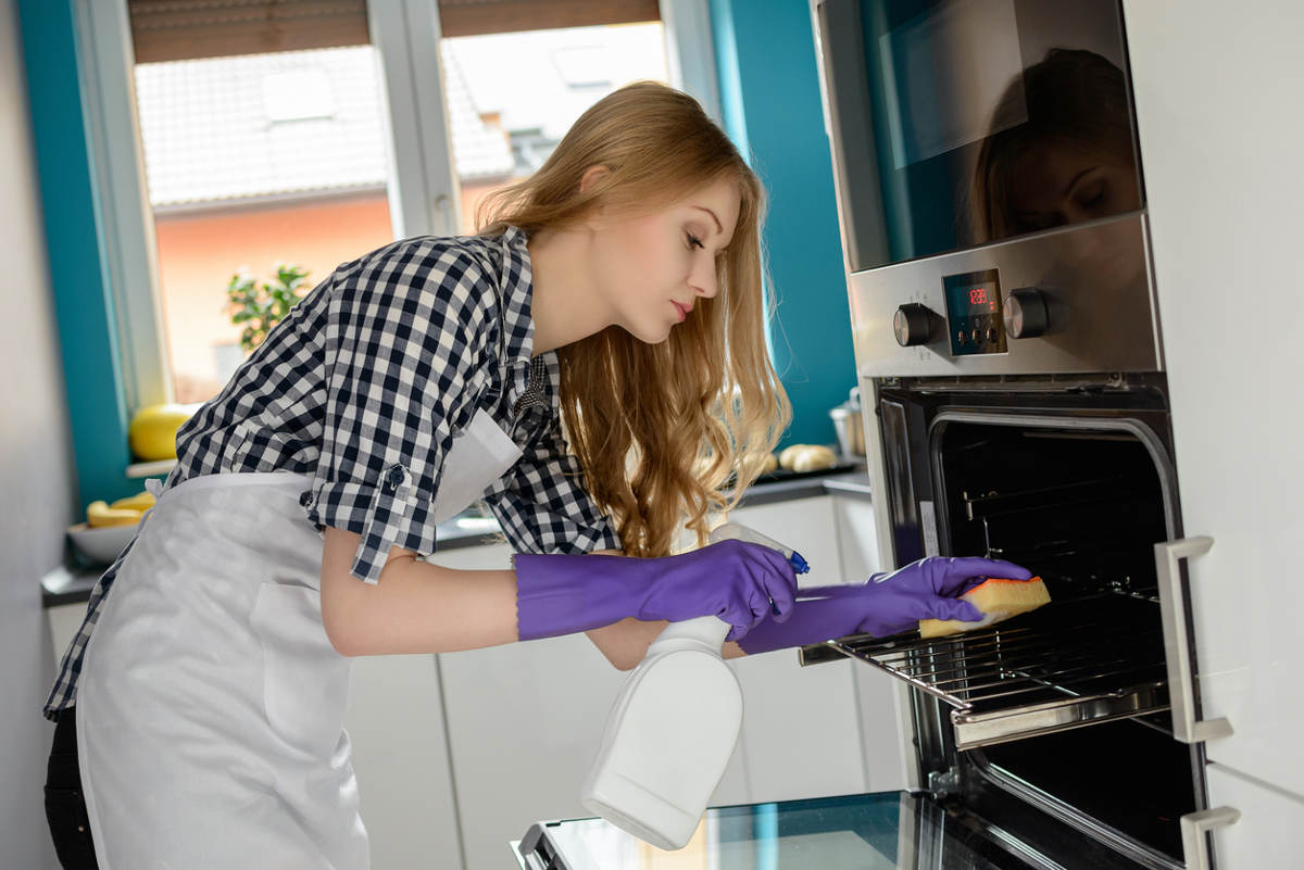Хозяйка моет духовку на кухне