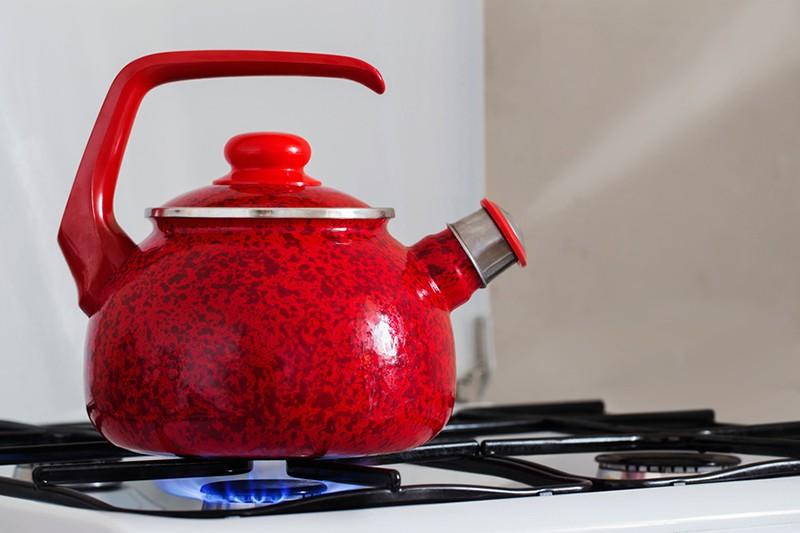 Красный чайник на плите