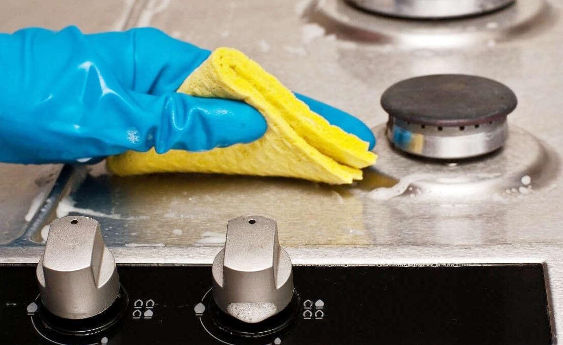 Моет кухонную плиту