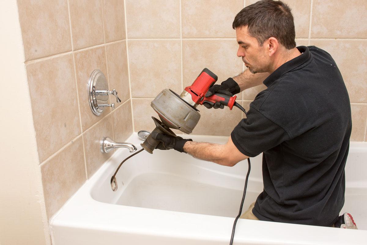 Сантехник прочищает ванну
