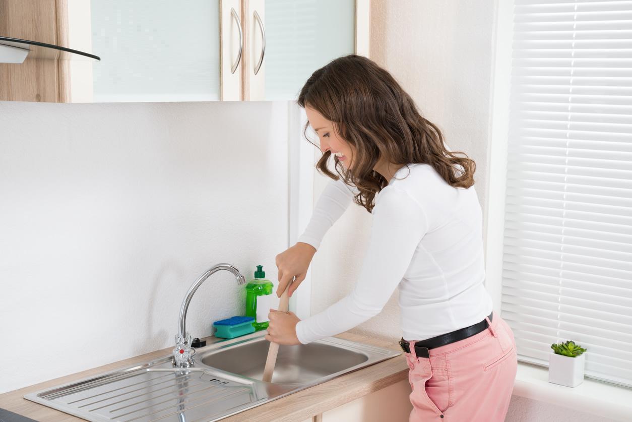 Женщина прочищает раковину