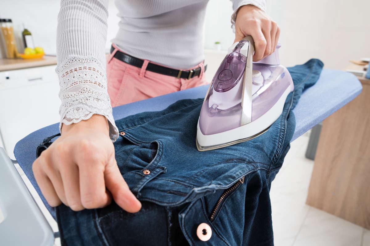 Гладит утюгом джинсы