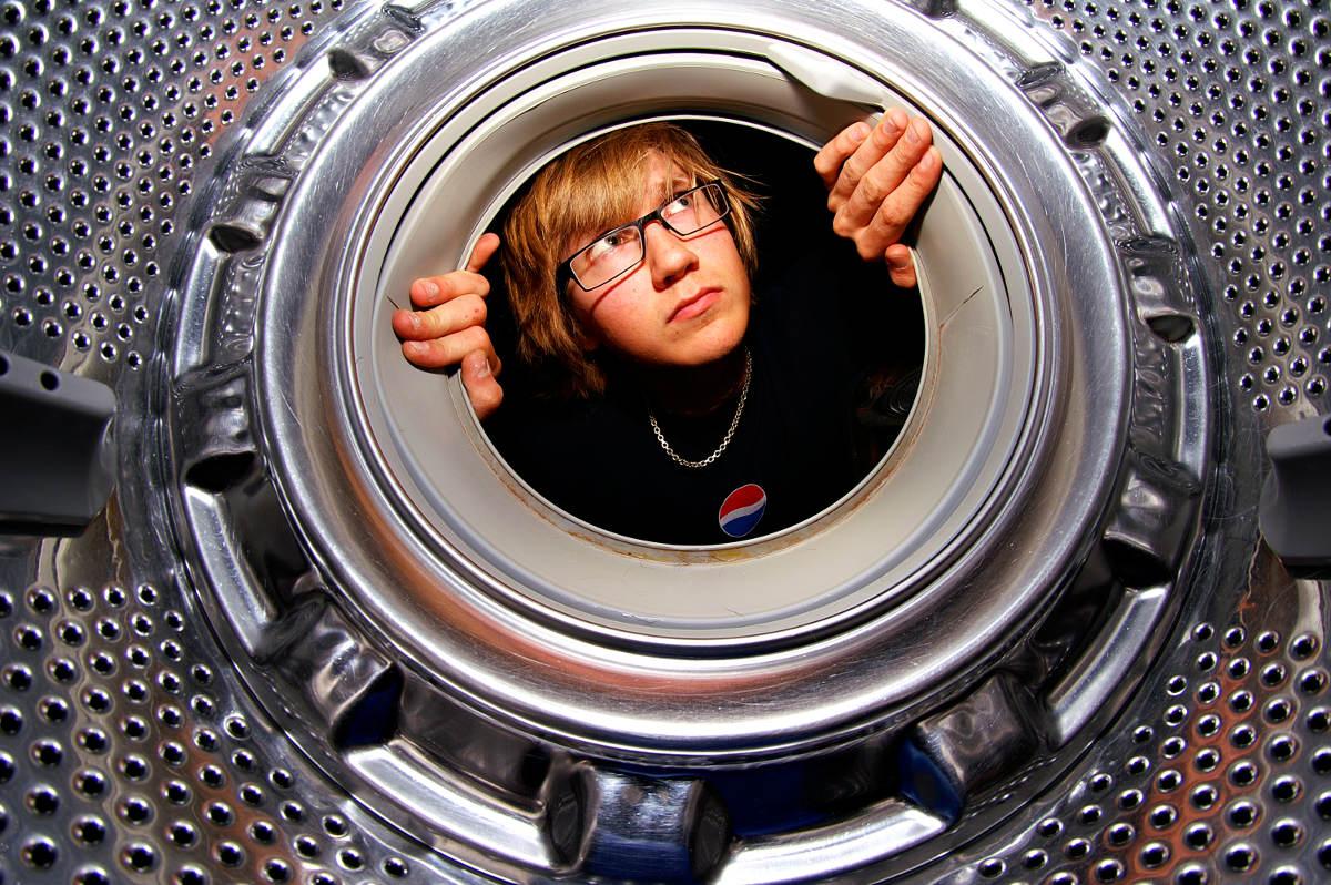 Человек смотрит в барабан стиральной машины