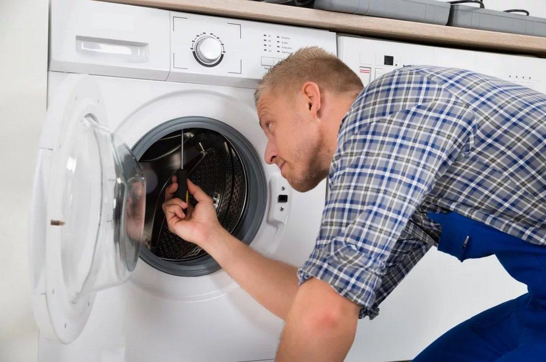 Мастер чинит стиральную машину