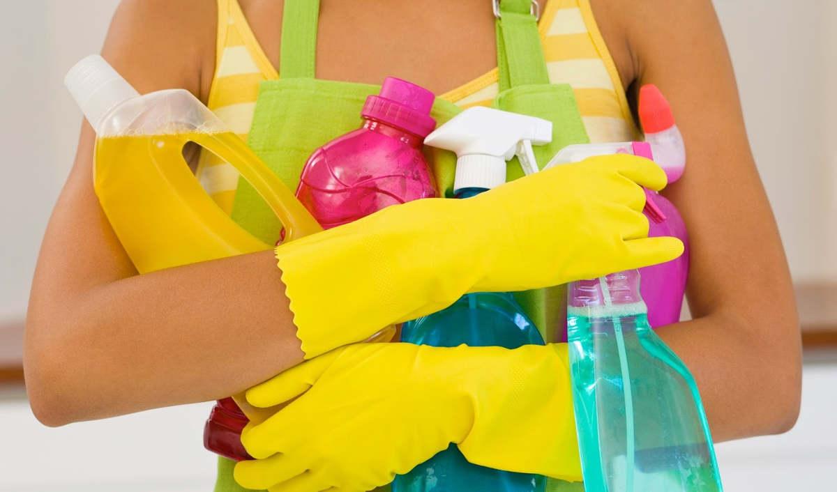 Женщина держит чистящие средства