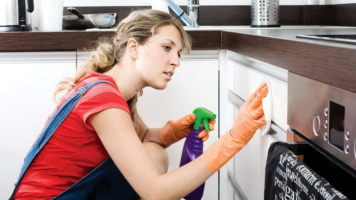 Женщина моет мебель на кухне