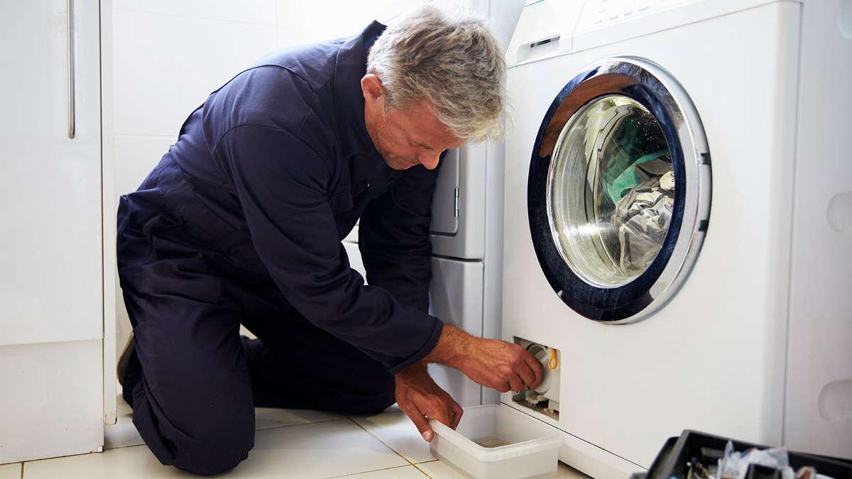 Мастер чистит фильтр стиральной машины