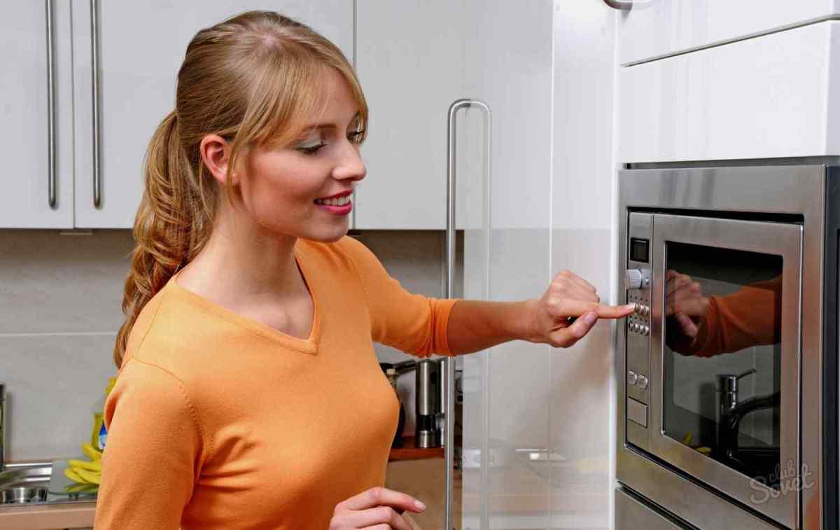 Женщина у микроволновки на кухне