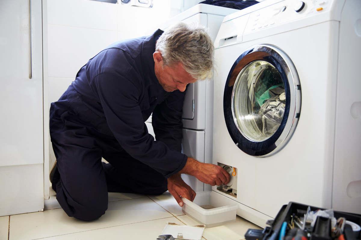 Мастер чистит стиральную машину
