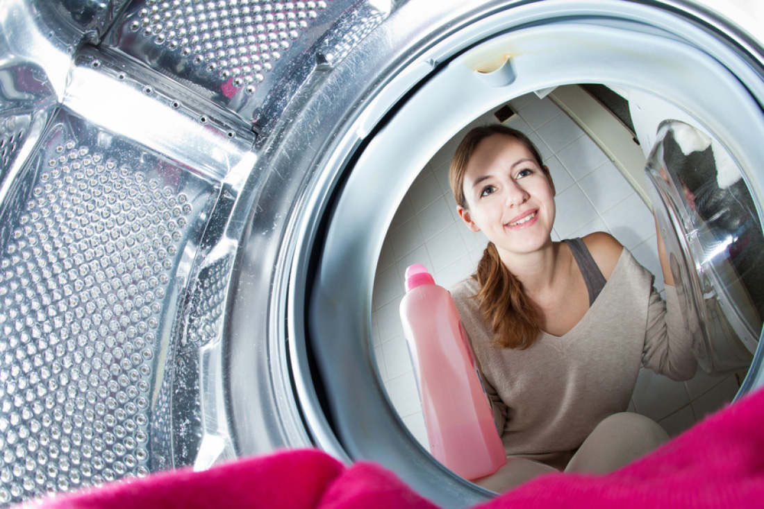 Женщина заглядывает в стиральную машину