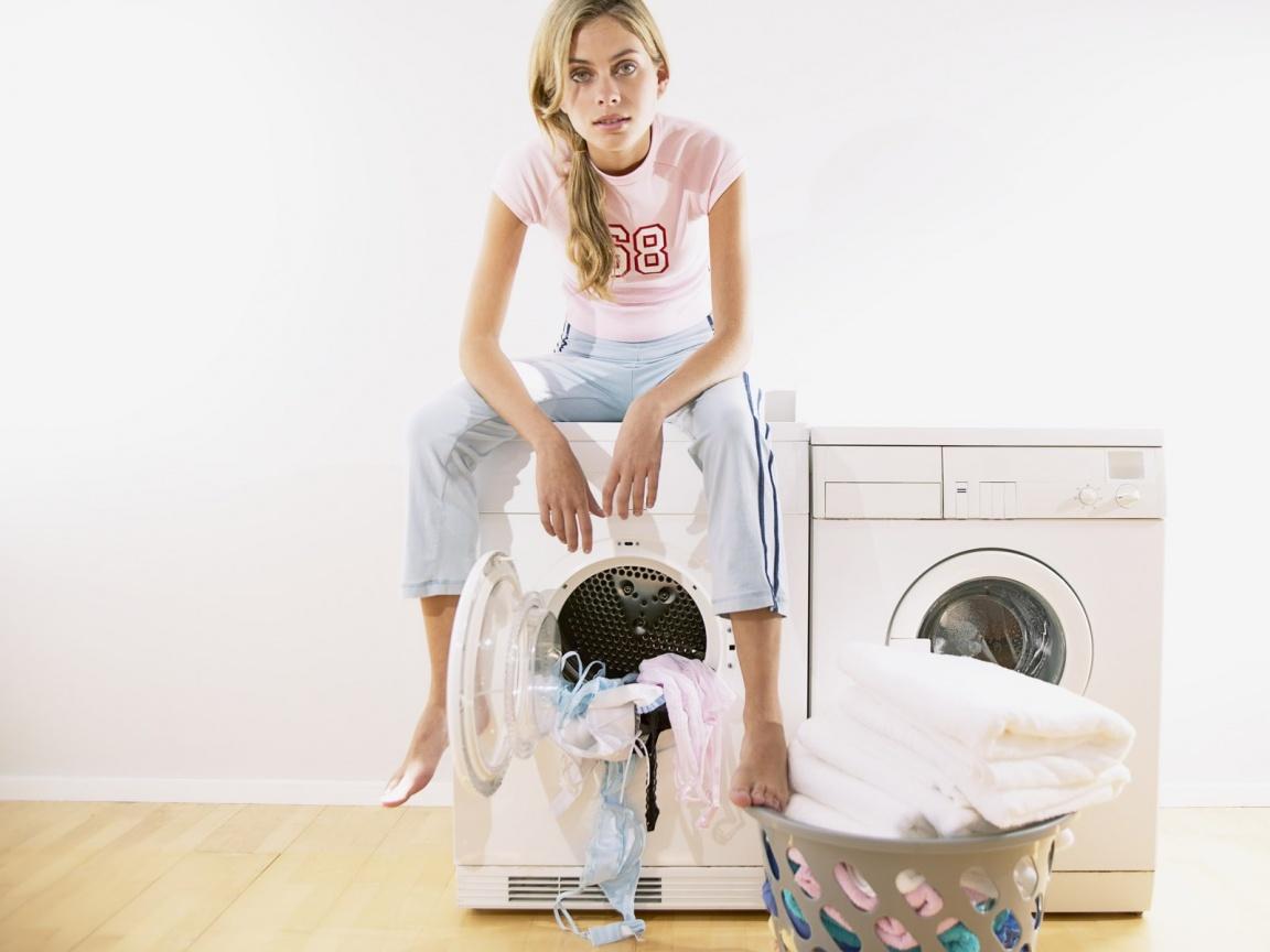 Женщина сидит на стиральной машине
