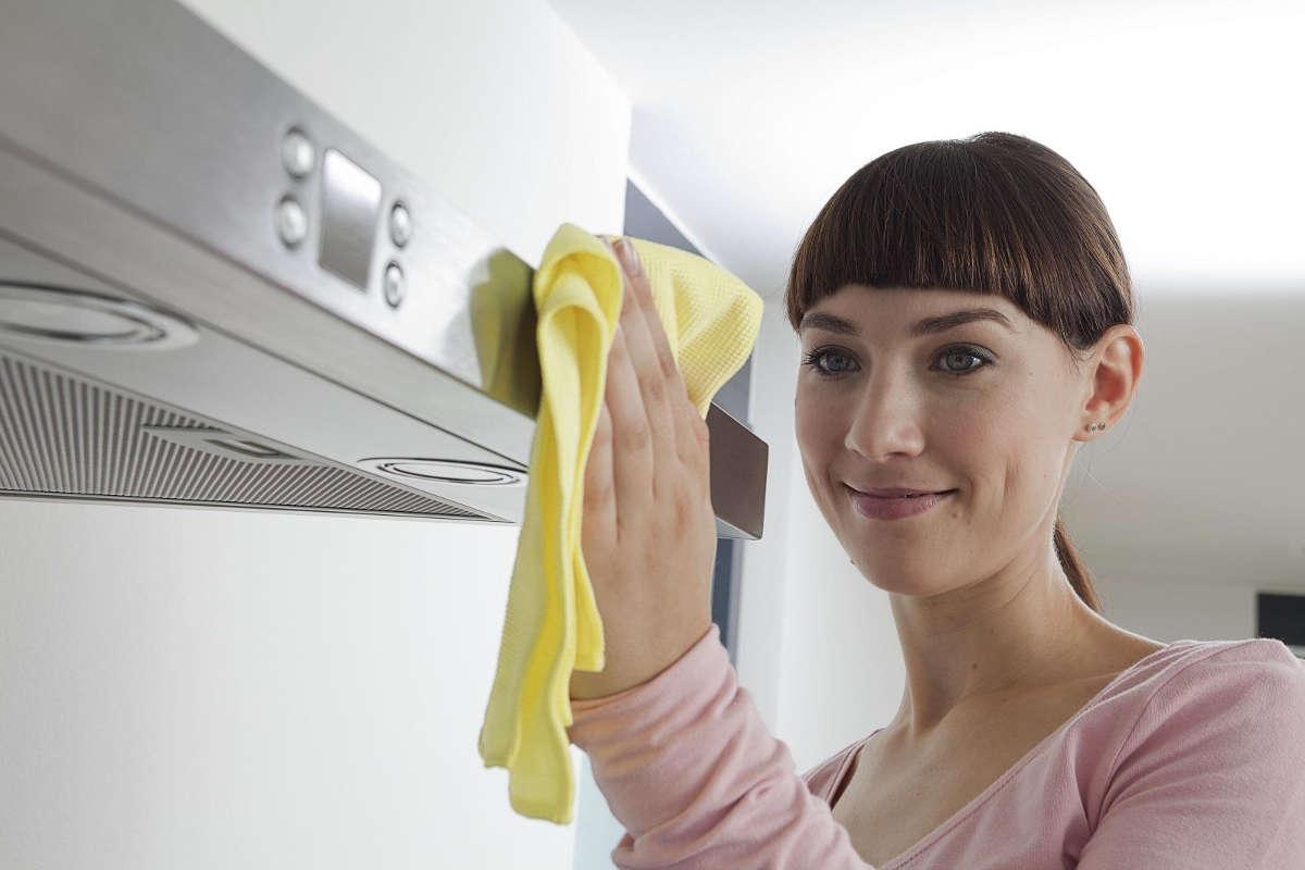 Женщина чистит вытяжку на кухне