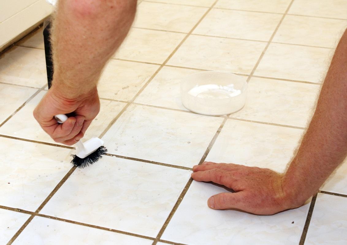 Мужчина чистит кафель