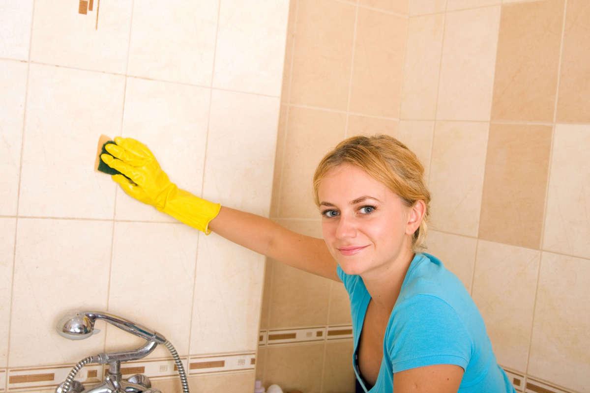 Женщина моет кафель в ванной