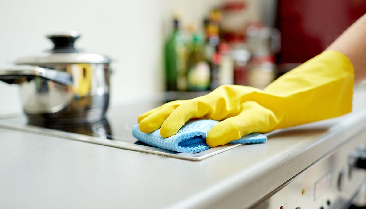 Рука в жёлтой перчатке на кухонной плите