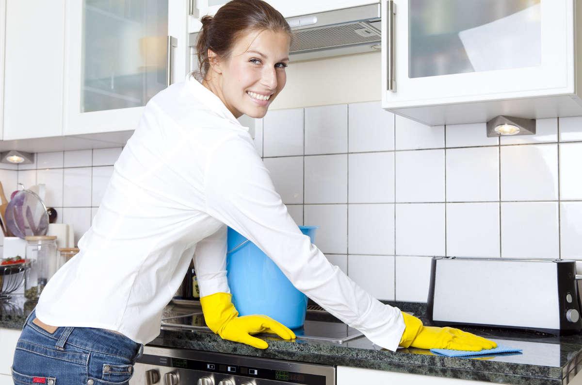 Женщина моет плиту на кухне