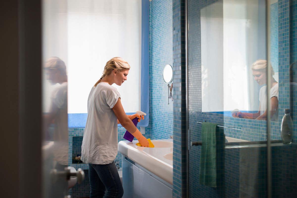 Женщина моет ванную комнату