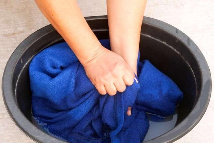 Стирает одежду в тазу