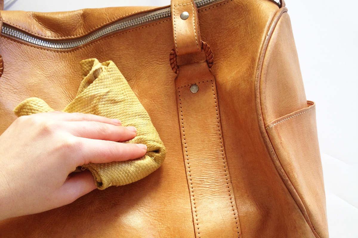 Чистит кожаную сумку