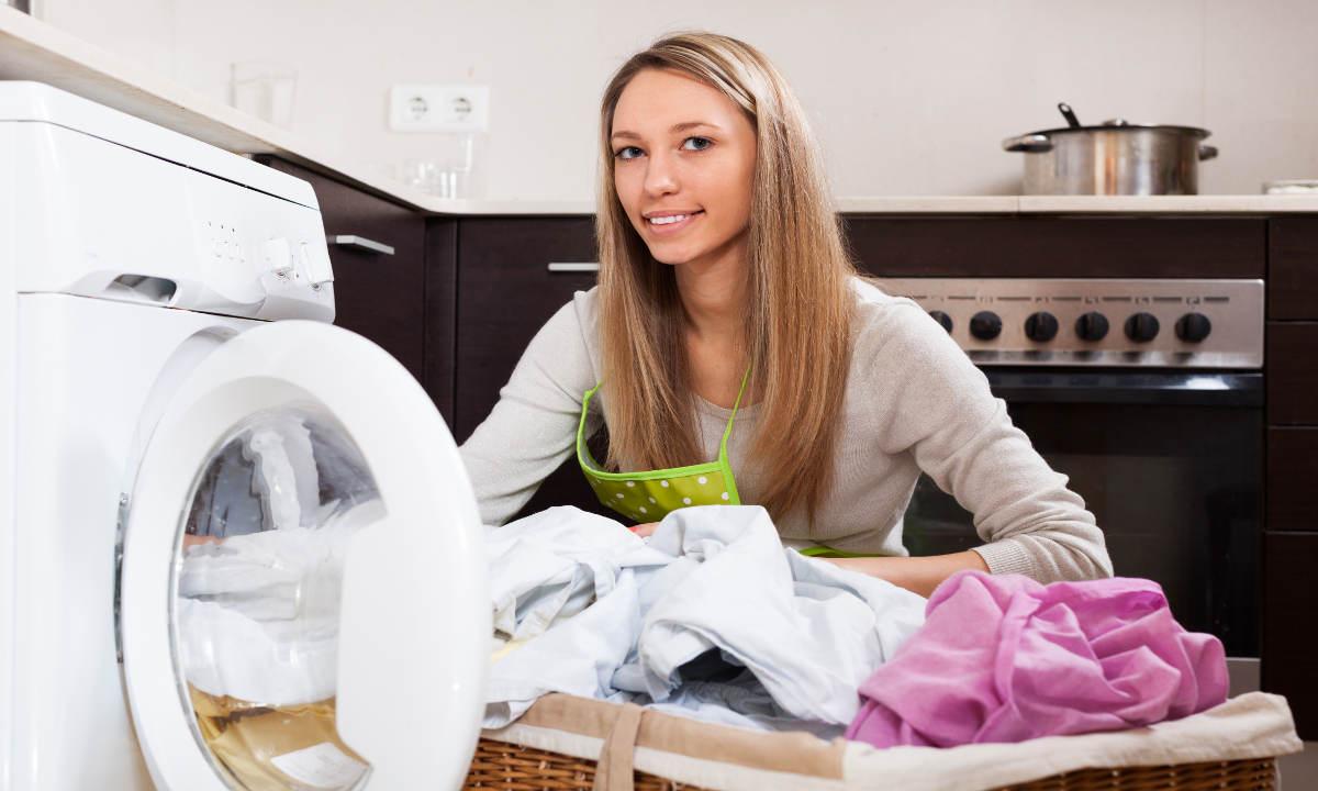 Хозяйка загружает бельё в стиральную машину