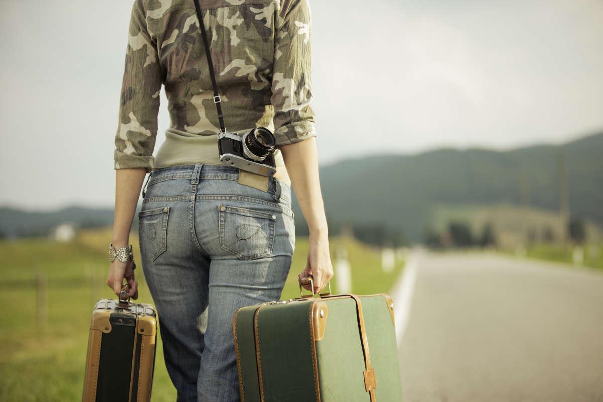 Девушка в джинсах идёт по дороге