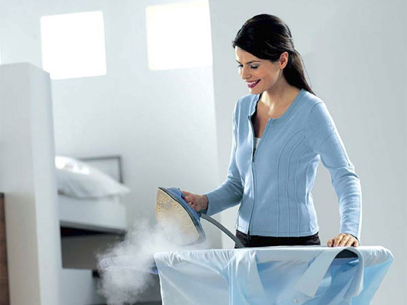 Девушка гладит одежду