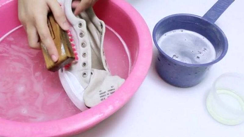 Моет кроссовки в тазу