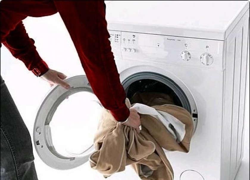 Загружает одежду в стиральную машину