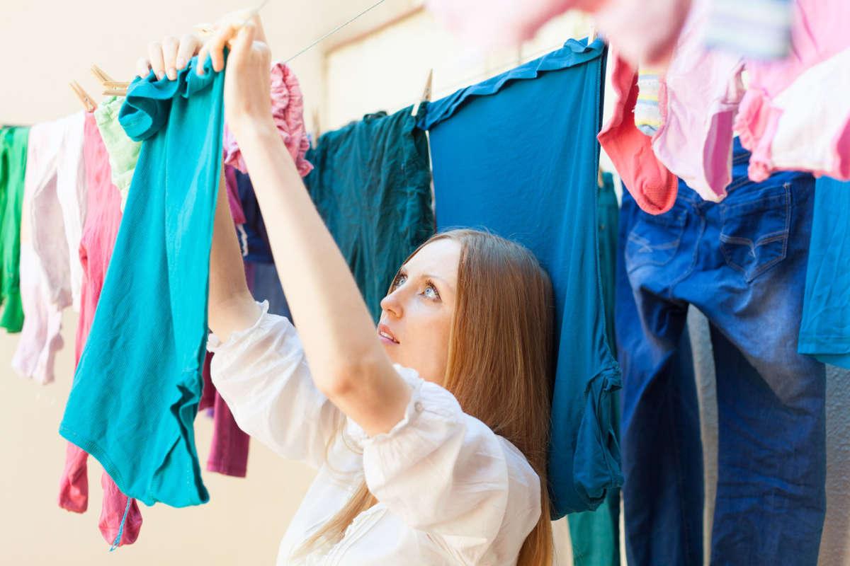 Женщина развешивает одежду на верёвках