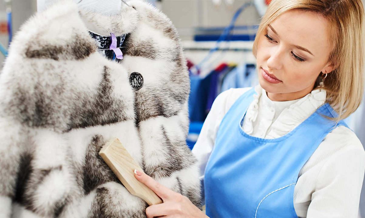 Женщина чистит белую шубу