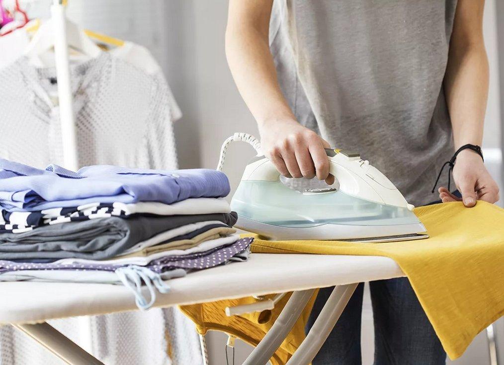 Гладит одежду утюгом