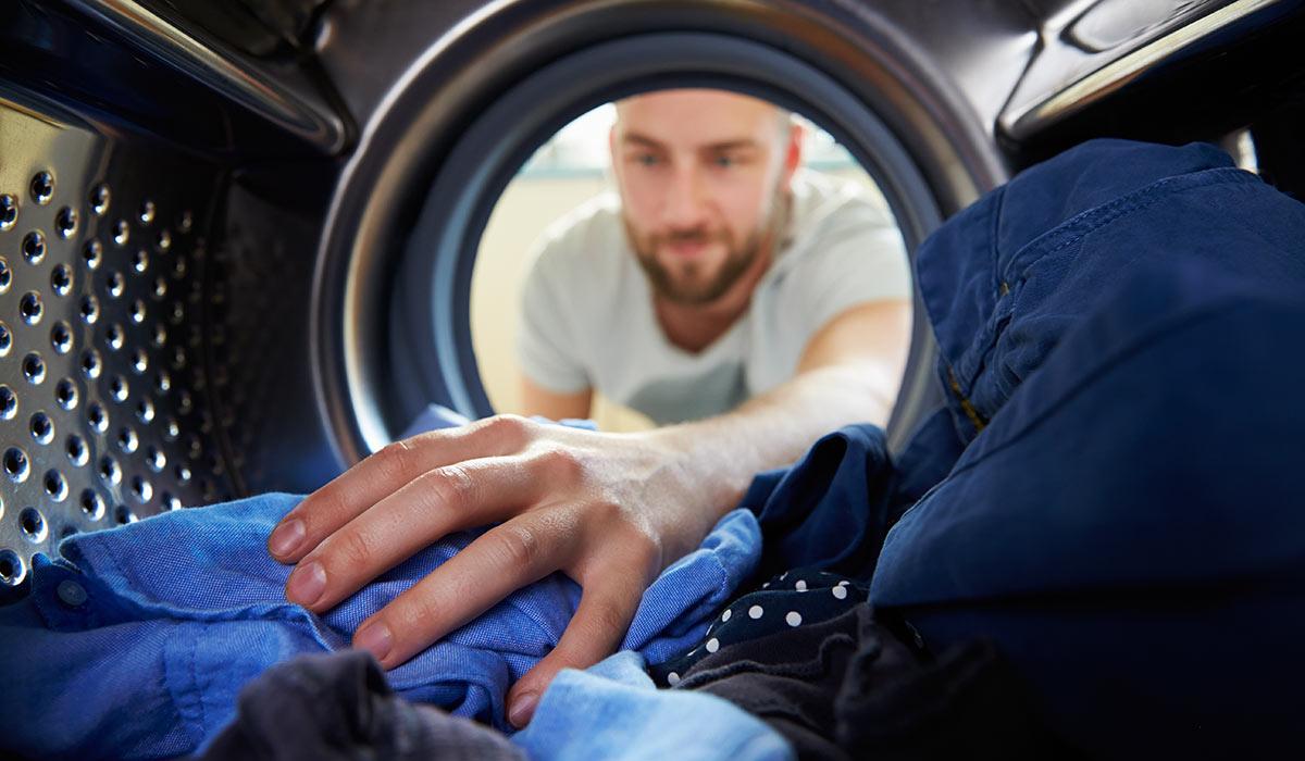 Мужчина стирает одежду в машине