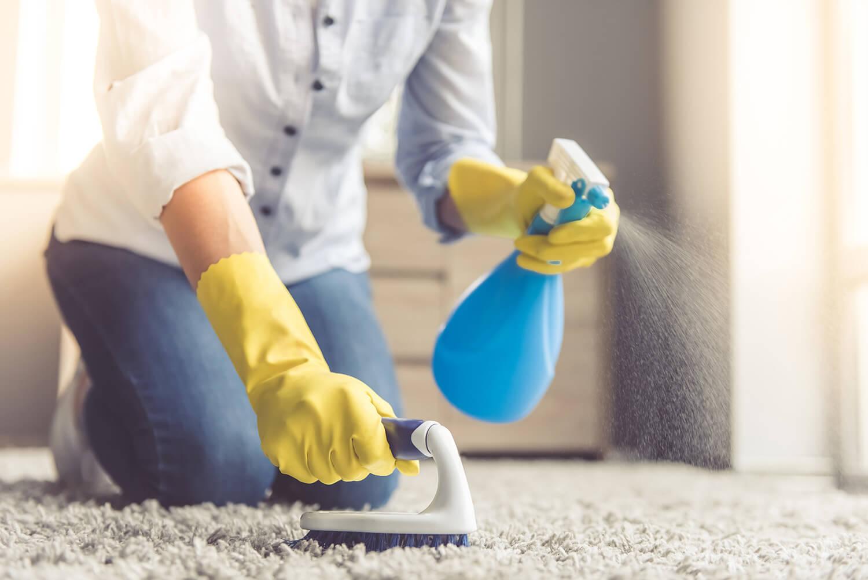 Женщина чистит ковёр