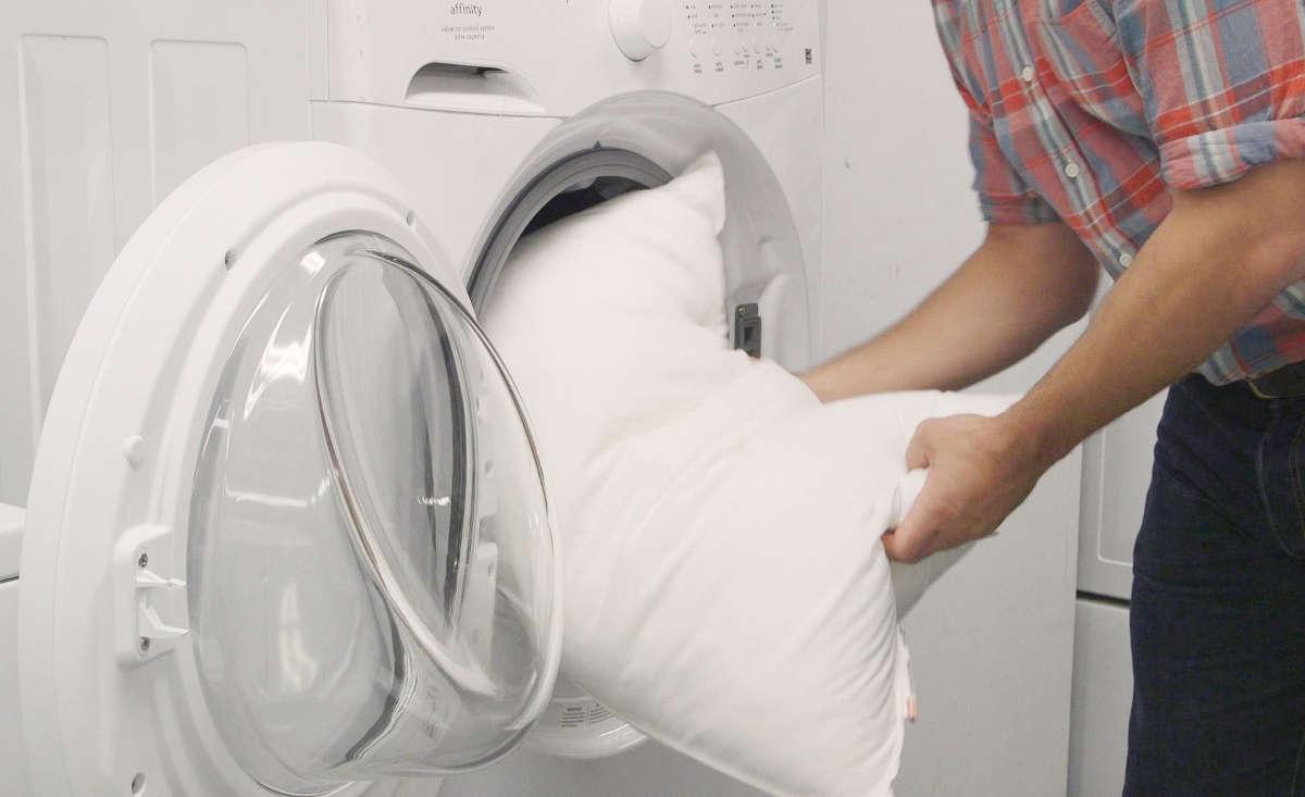 Мужчина стирает подушку