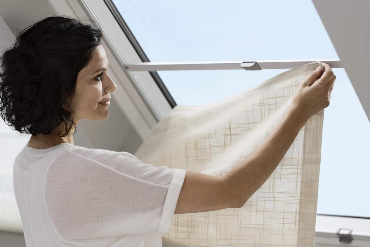 Девушка развешивает шторы