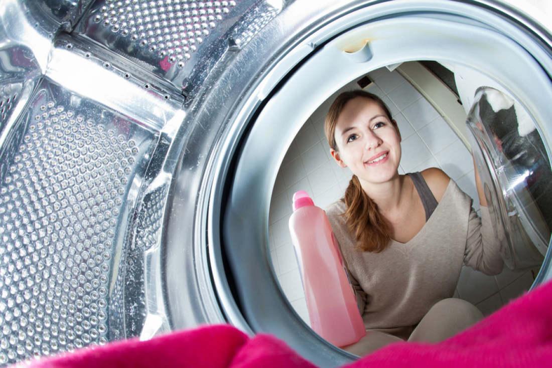 Девушка стирает одежду в машине